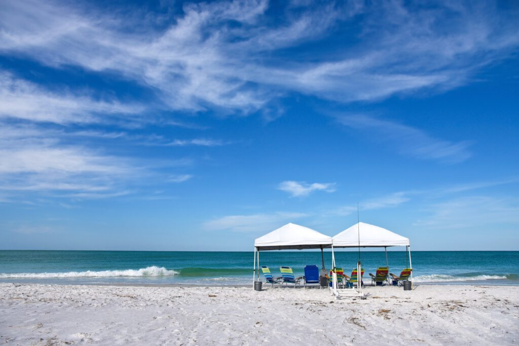 Two Portable Canopy's with Lounge Chairs set up to provide shade on the Beach
