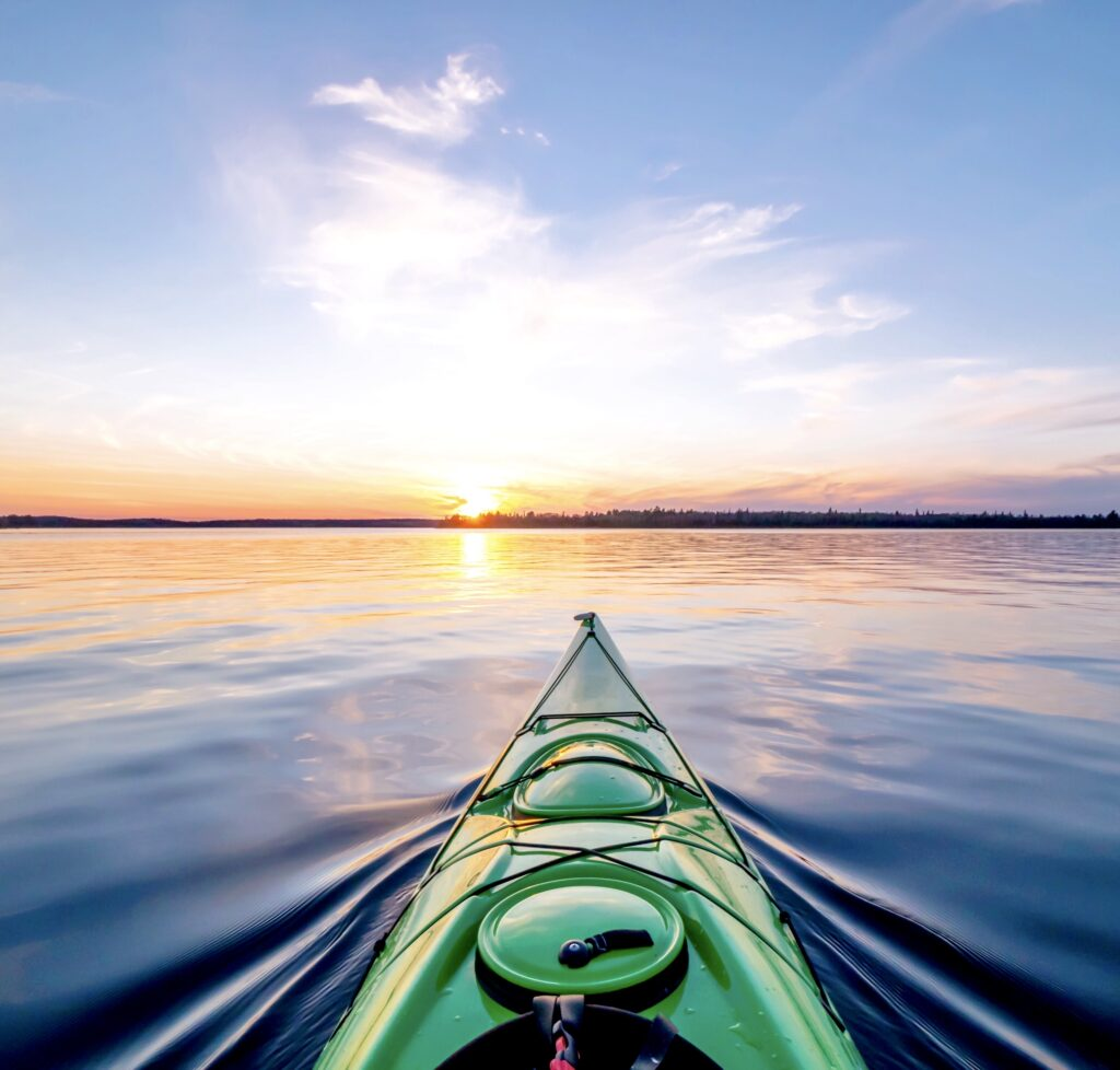 Kayaking at sunset on a calm lake in Northwest Ontario, Canada.